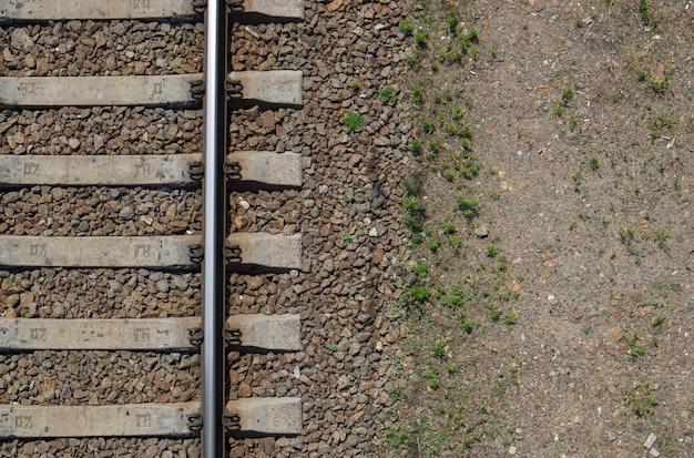 Spoorweg bovenaanzicht, plat gelegd. een deel van het spoor voor treinen. luchtfoto van een spoorlijn vanuit een drone. achtergrond met ruimte voor tekst. glanzende ijzeren rails en betonnen dwarsliggers.
