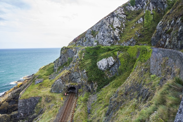 Spoorweg door de berg van steenrotsen bij ierse zeekust. bray, greystone