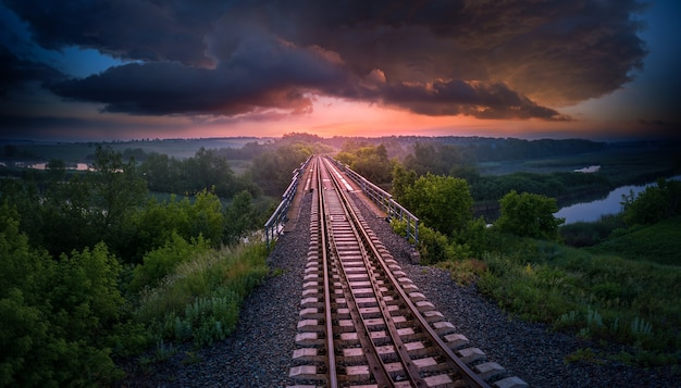 Spoorweg en brug over de rivier op een achtergrond van zonsondergang en onweerswolken. luchtfoto. mooi zomeravondlandschap.