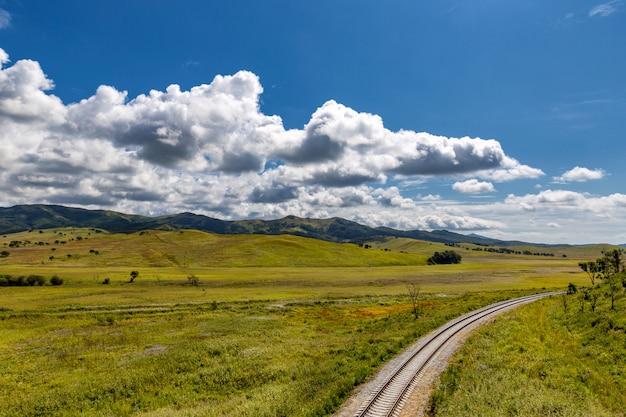 Spoorweg en plattelandslandschap met groene heuvels en blauwe hemel