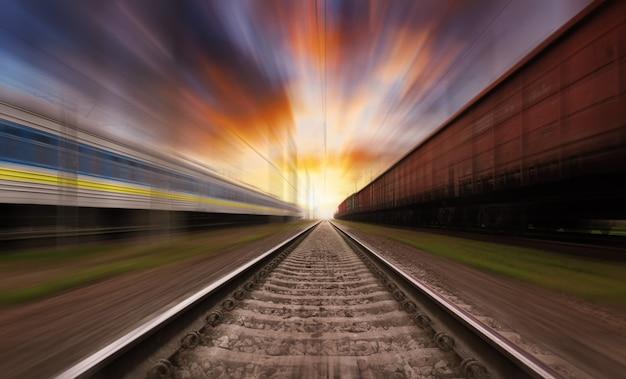 Spoorweg in beweging bij zonsondergang met dramatische hemel. bewegingsonscherpte-effect.