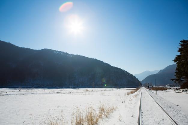 Spoorweg in de winter met zon