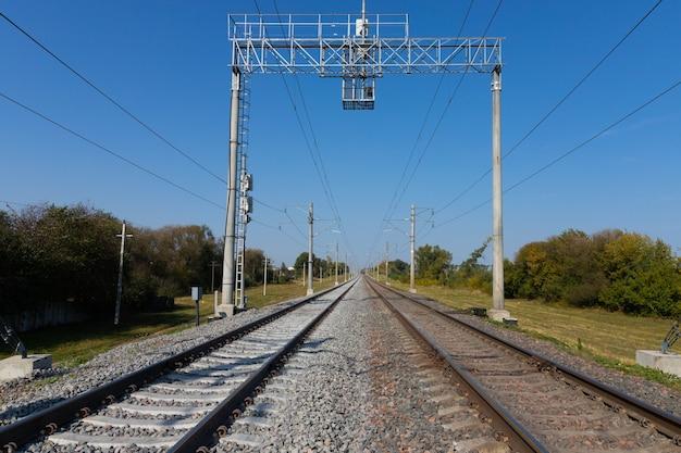 Spoorweg met elektrische draden die in de verte gaan.