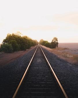 Spoorweg op het platteland onder een gouden hemel