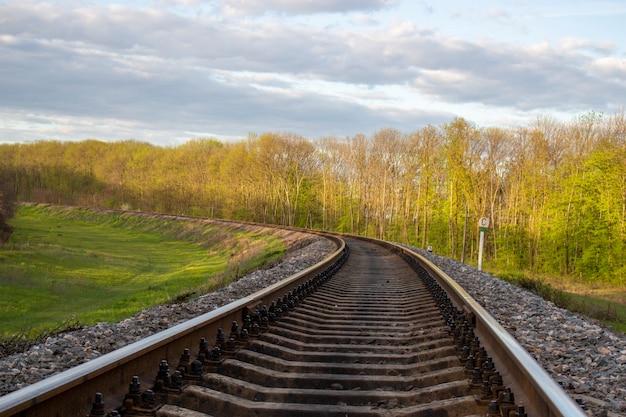 Spoorwegen in de stad, natuur en bomen aan weerszijden.