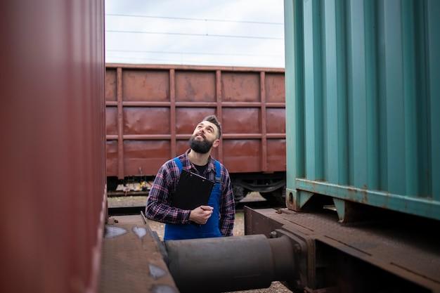 Spoorwegman treintrailers controleren voor vertrek