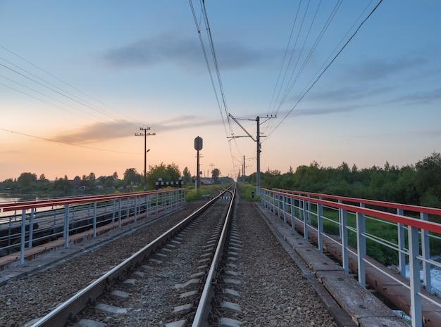 Spoorwegsporen op de brug door het platteland in de avond