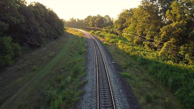 Spoorwegverkeer van de schaduw van bomen naar het ochtendzonlicht.