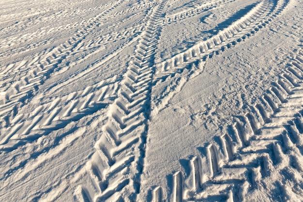 Sporen achtergelaten in de sneeuw van auto's op een ongeschilde weg na een sneeuwval, een weg bedekt met sneeuw in de winter,