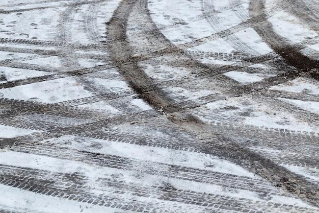 Sporen op witte sneeuwsporen van de wielen van auto's