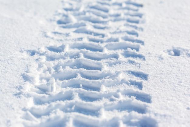 Sporen van autowielen in de sneeuw