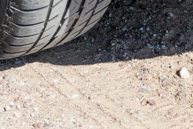Sporen van de wielen van auto's op de weg van het zand, close-up op de weg