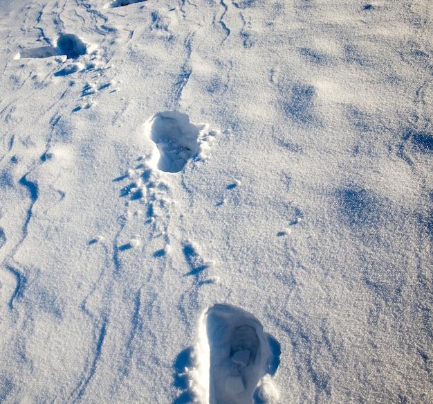 Sporen van een persoon in de sneeuw, close-up in het winterseizoen