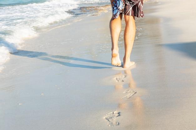 Sporen van mannelijke voeten op het zandstrand van de zee op een zonnige dag.
