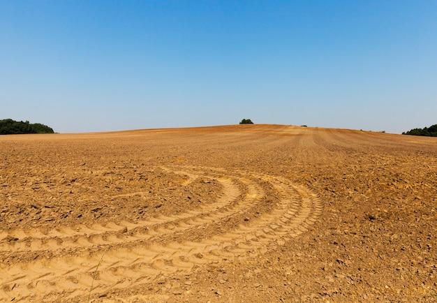 Sporen van wiel geploegd landbouwgebied dat overblijft na de speciale uitrusting, de blauwe lucht op de achtergrond
