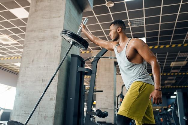 Sporsman oefening met barbell in sportschool doet