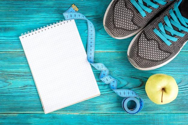 Sport achtergrond sneakers, tape, notebook en appel op blauw hout, plat leggen