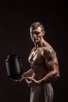 Sport achtergronden. sterke bodybuilder die een plastic kruik met een droge geïsoleerde proteïne houdt. sport eten