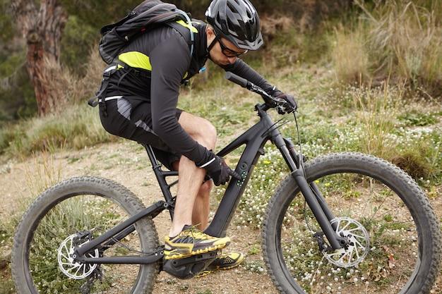 Sport, actieve levensstijl, fitness, extreme en adrenaline concept. openluchtschot van knappe fietser in beschermende uitrusting die knopen op controlebord op zijn pedelec drukken, die snelheidswijze schakelen