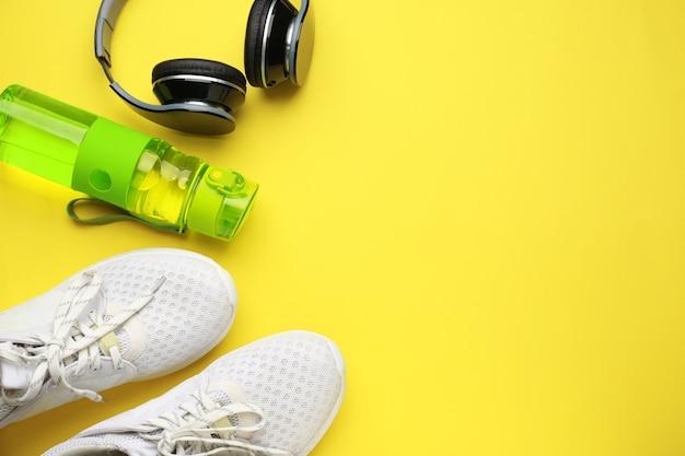 Sport bidon, koptelefoon en schoenen op kleur