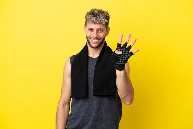 Sport blanke man geïsoleerd op gele achtergrond gelukkig en vier tellen met vingers