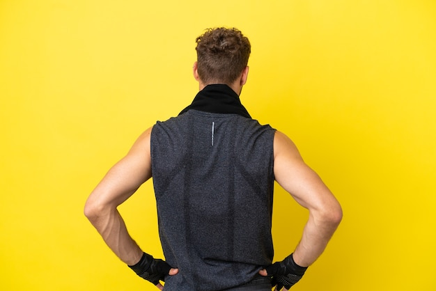 Sport blanke man geïsoleerd op gele achtergrond in achterpositie