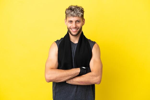Sport blanke man geïsoleerd op gele achtergrond met de armen gekruist in frontale positie