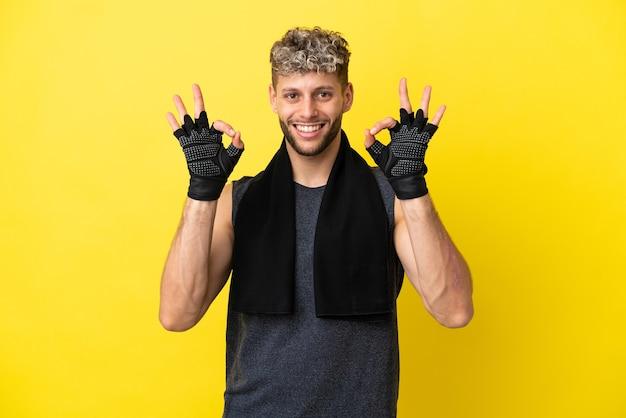 Sport blanke man geïsoleerd op gele achtergrond met een ok teken met vingers