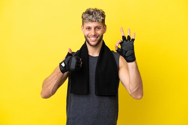Sport blanke man geïsoleerd op gele achtergrond met ok teken en duim omhoog gebaar
