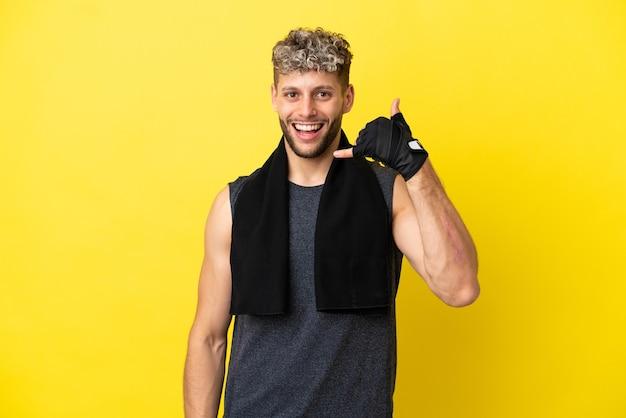Sport blanke man geïsoleerd op gele achtergrond telefoon gebaar maken. bel me terug teken