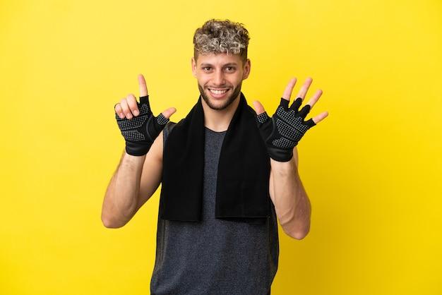 Sport blanke man geïsoleerd op gele achtergrond tellen zeven met vingers