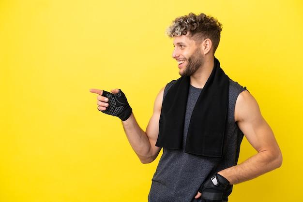Sport blanke man geïsoleerd op gele achtergrond wijzende vinger naar de zijkant en presenteren van een product