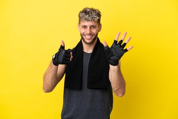 Sport blanke man geïsoleerd op gele achtergrond zes tellen met vingers