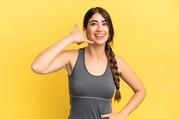 Sport blanke vrouw geïsoleerd op gele achtergrond telefoon gebaar maken. bel me terug teken