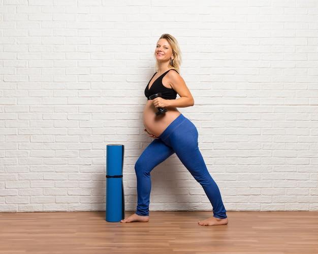 Sport blonde zwangere vrouw doen oefening binnenshuis maken van gewichtheffen