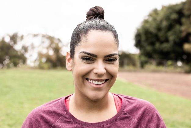 Sport bochtige vrouw die lacht buitenshuis in stadspark - focus op gezicht