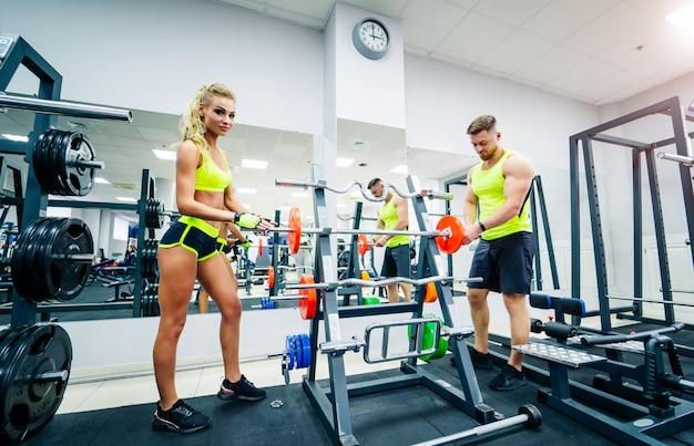Sport, bodybuilding, lifestyle en mensen concept. de jonge vrouw volgt haar persoonlijke traineruitleg. barbell tillen.