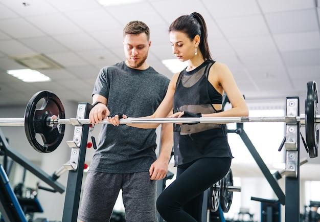 Sport, bodybuilding, lifestyle en mensen concept - jonge man en vrouw met barbell buigende spieren en schouderpers squat maken in de sportschool. trainer en fitness meisje hebben training in de sportschool.