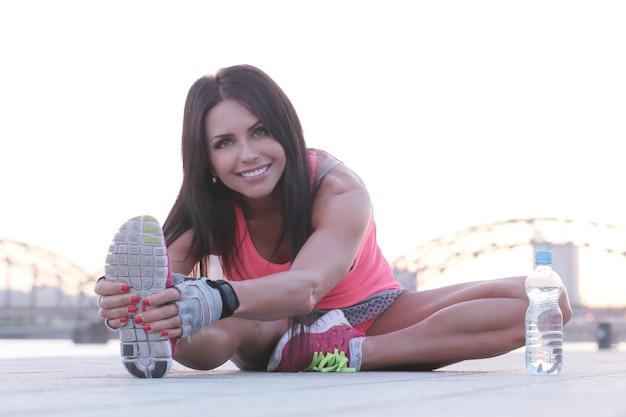Sport buiten, vrouw die zich uitstrekt