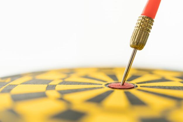 Sport, business, doel, planning en doel concept. sluit omhoog van rood pijltjeskant dat op centrum van zwart en geel dartboard wordt geraakt