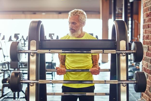 Sport en bodybuilding concept sterke volwassen man in sportkleding tillen gewogen bar of barbell
