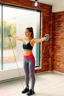 Sport en een gezonde levensstijl. vrouw in de sportschool doet oefeningen om de spieren te versterken met behulp van sportartikelen.
