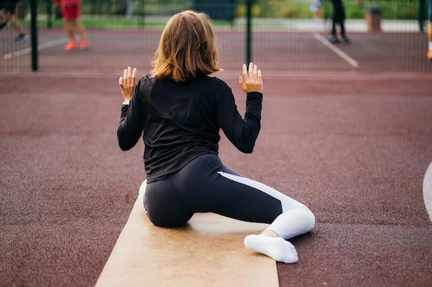 Sport en fitness buiten de sportschool. jonge fit vrouw in sportkleding traint buiten op de speelplaats.