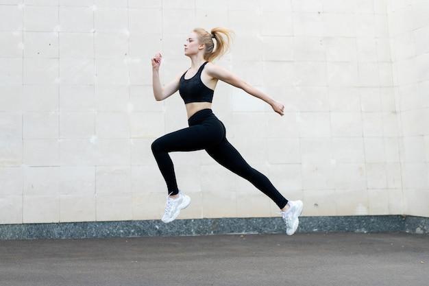 Sport en fitness concept jonge volwassen blanke vrouwelijke atleet springen hoog buiten grijze staart muur achtergrond sportieve vrouw springen oefeningen buiten gezonde levensstijl motivatie