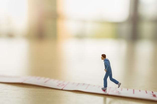 Sport en fitness concept. sluit omhoog van miniatuur het cijfermensen die van de mensenagent op maatregelenband lopen op houten lijst met exemplaarruimte