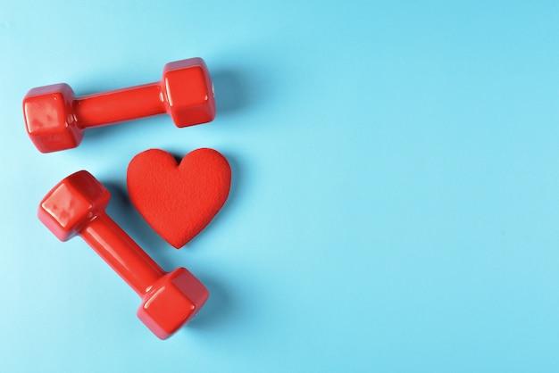 Sport en fitness conceptenachtergrond met copyspace met rood hart en domoren op blauwe zwarte grond. bovenaanzicht