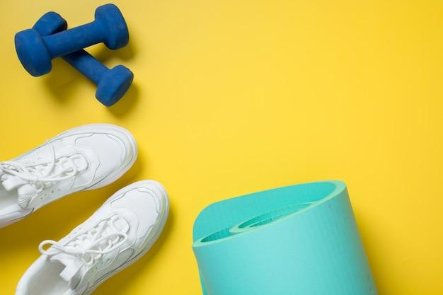 Sport- en fitnessschoenen, halter, yogamat op geel. ruimte voor tekst.