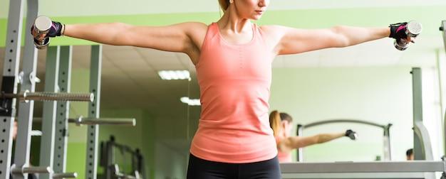 Sport en recreatie concept - sportieve vrouw handen met halters.