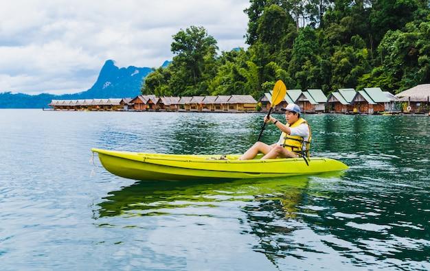 Sport en recreatie. de jonge mens geniet vakantie van kajak in cheow lan lake, thailand