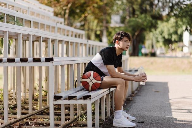 Sport- en recreatieconcept een jonge mannelijke basketbalspeler zittend op een tribune aan de rand van het sportveld.